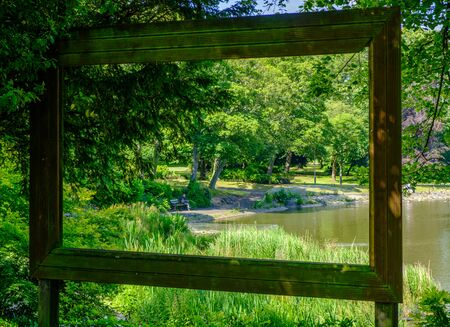Newcastle, United Kingdom -July 1, 2019: View through large hollow picture frame of a pond, trees and a man sitting on a bench at Leases Park in Newcastle, England