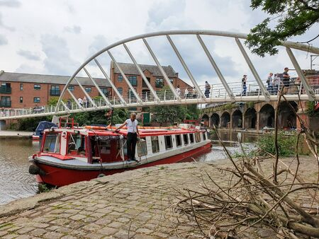 Manchester, United Kingdom - August 3, 2019: A bearded man stands on a narrowboat in Castlefield district in Machester, UK