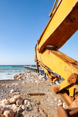 Scoop of an excavator set against a pier at the seafront in Argaka in the island of Cyprus.