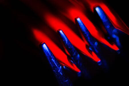 Two forks in colorful illumination macro shot creating an abstract composition. Image is suitable as a background.