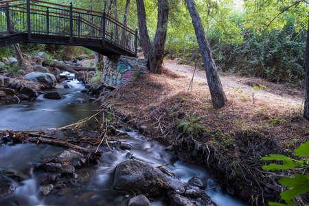Bridge over smooth flowing water stream at the Vateri Footpah in Kakopetria, Troodos, Cyprus