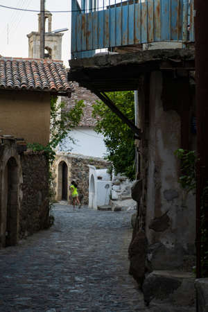 Picturesque narrow streets of old Kakopetria in the Troodos mountains in Cyprus with a girl walking in the distance
