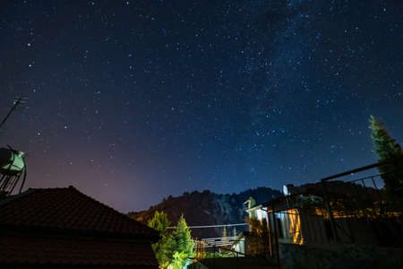 Stars and Milky Way over the forest and a house at the Troodos mountains in Kakopetria village in Cyprus Imagens