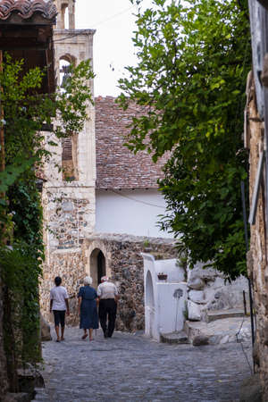 People strolling in the picturesque narrow streets of old Kakopetria in the Troodos mountains in Cyprus with a girl walking in the distance Editöryel