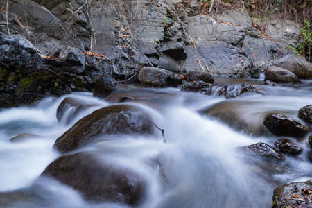 Pure water stream with smooth flow over rocky mountain terrain in the Kakopetria forest in Troodos, Cyprus. Slow exposure creating sooth flow impression. Stok Fotoğraf