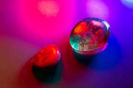 Two tumbled mineral gems colorfully illuminated showing abstract details.