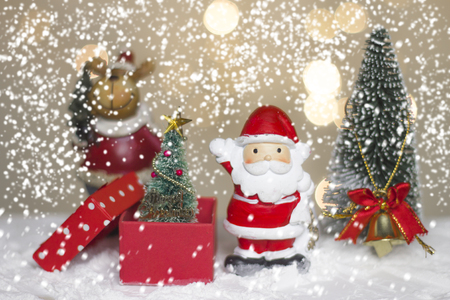 Miniature Christmas Santa cros and Tree on snow over blurred bokeh background,Decoration Image for Christmas Holiday and Happy New Year Gift box Celebration concept.