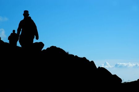 Silhouette of a climbers on blue background Stock Photo