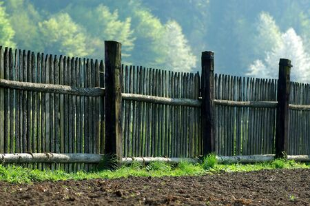 midst: Old fence in the midst of brown field and trees
