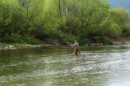 fishing pole: Fisherman angling on the river Stock Photo