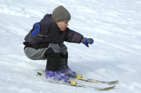 skischool: Young boy skiing cerefully down