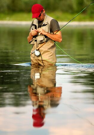 wade: A fisherman make ready angling on the river Stock Photo