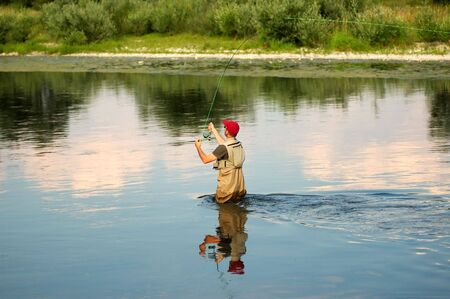 Fisherman angling on the river Stock Photo