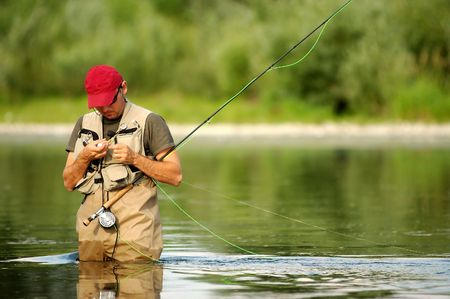 botas altas: Un pescador hace pescar con caña listo en el río
