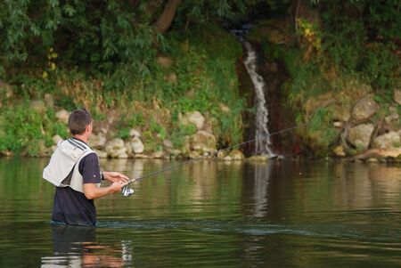 waders:  Fisherman angling on the river Stock Photo