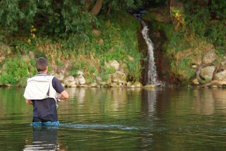 fishingpole: Fisherman angling on the river Stock Photo