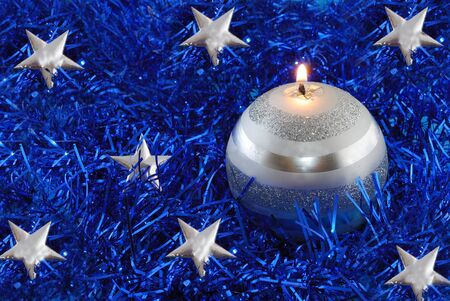 unlike: Christmas candle, decorations on tinsel Stock Photo