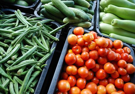 Fresh assorted vegetables in boxes on market photo