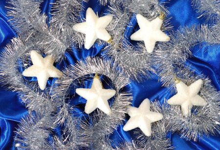 sateen: Christmas decoration on blue sateen with big stars on tinsel
