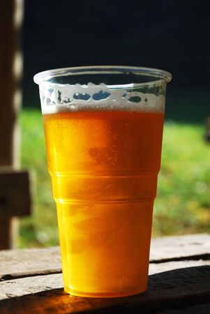 Plastic cup of beer on the table