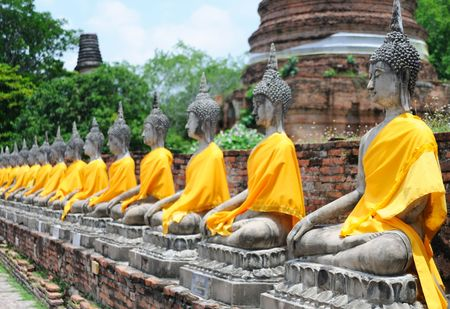 ancient yoga: Aligned buddha statues with orange bands, Thailand Stock Photo