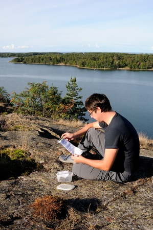 A young man finding a geocache Stock Photo