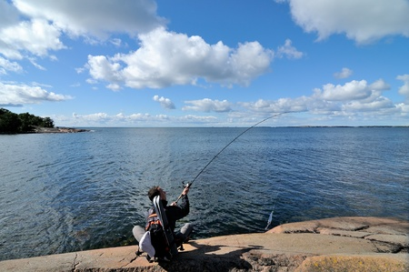A fisherman angling on the sea photo