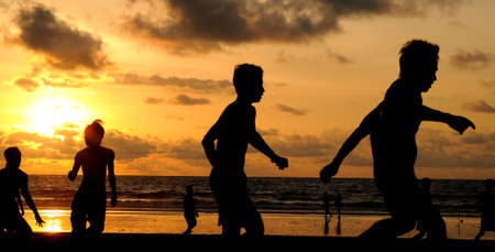 Silhouette of football players on the beach