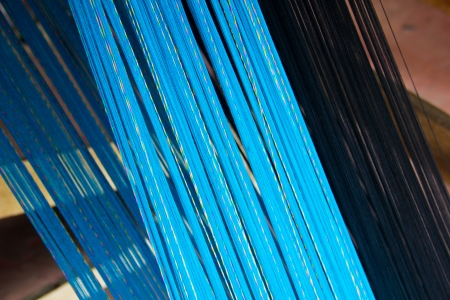 Blue and black cotton strings in weaving process Stock Photo