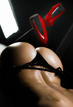 nice ass in black panties on a black background
