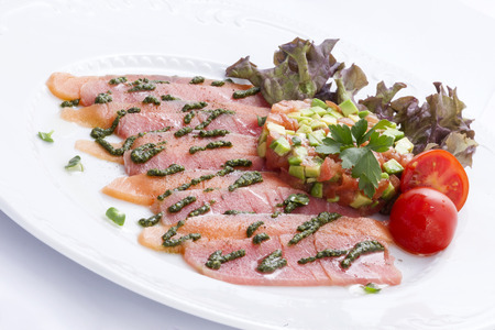 Carpaccio of tuna and salmon flavored with pesto and avocado tartare and tomato fillets kankase Standard-Bild