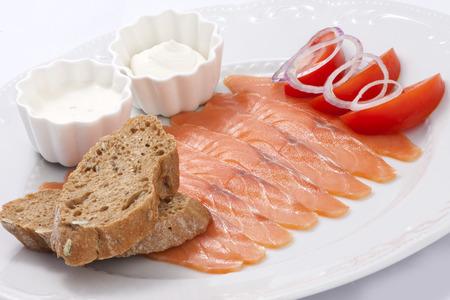 Mild gesalzen Lachs mit Sauce und Toast mit Tomaten und Zwiebeln geschmückt