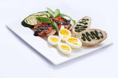Frühstück Toast mit Pesto-Sauce, Eier und Tomaten mit Mozzarella-Käse, gebratenen Zucchini, und nicht viel Avocado.