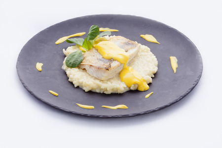 roasted fillet of cod on a bed of risotto flavored sauce and carnations Standard-Bild