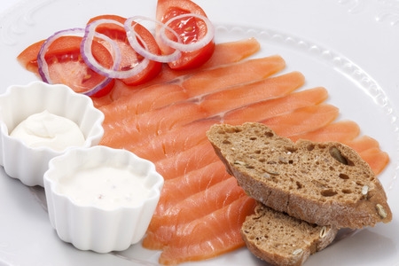 Mild salted salmon with sauce and toast decorated with tomatoes and onions