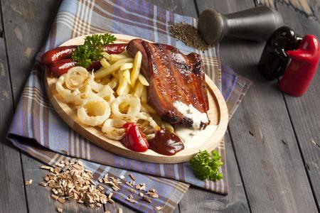 Rippen und Würstchen mit Pommes und Zwiebelringen. Perfekt für Bier