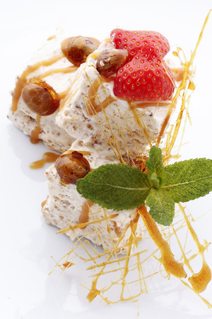 Homemade ice cream with caramel and strawberry decorated with mint leaves