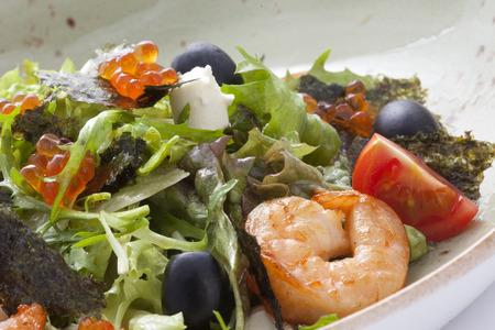 Rucola-Salat mit Garnelen, Käse, schwarzen Oliven mit Kaviar dekoriert.