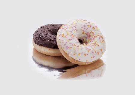 two donuts with chocolate and icing on a white background