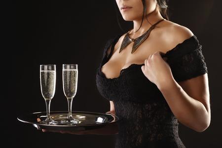 Girl waiter with two wine glasses on a dark background Standard-Bild
