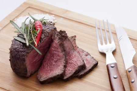Steak mit Gewürzen auf einer Holzwand, in der Nähe der Gabel und Messer