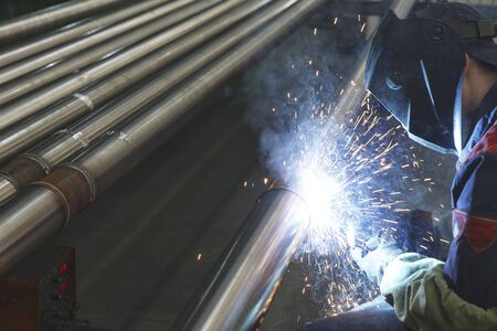 Welder electrically welds metal pipes, Selective focus Stockfoto