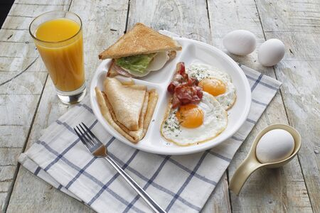 Breakfast of scrambled eggs with bacon, pancakes, sandwich and orange juice on a wooden table
