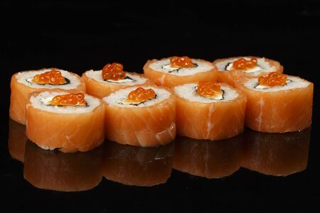 various sushi, rolls on a black background with reflection. especially for cafes and restaurants