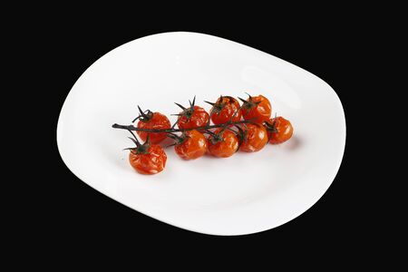 baked tomatoes on a branch in a white plate