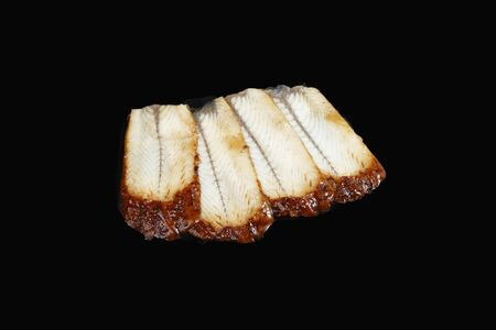 sliced smoked eel on black background Stock Photo - 128820168