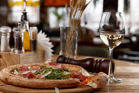 pizza with jamon and herbs on a wooden table