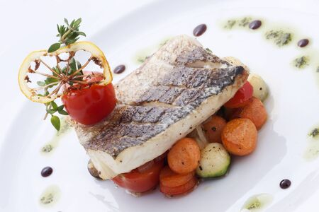 Halibut Steak with Vegetables and Sauce on a white background