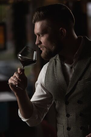 Professional sommelier man with a glass of red wine. selective focus