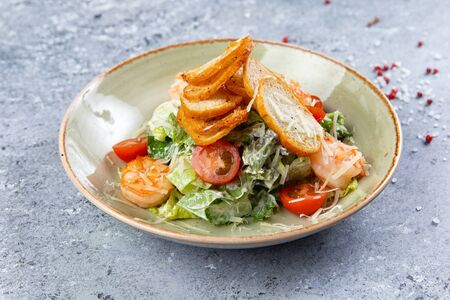 salad with shrimps and croutons in a plate on a gray background